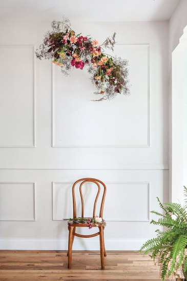 In a sunlight-filled, elegant white room, a suspended floral arrangement hangs above a simple wooden chair
