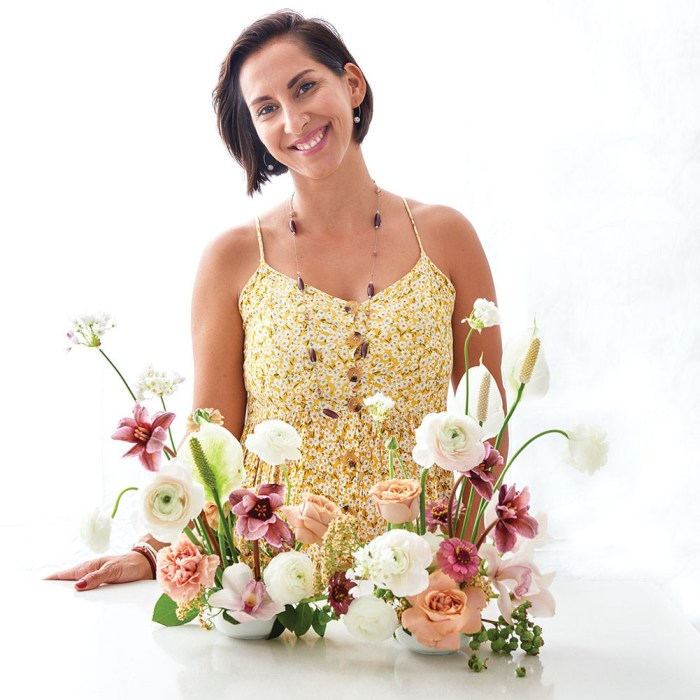 Portrait of floral designer Monica Delgado, with bobbed dark hair, wearing a yellow floral sundress and a long beaded necklace, stands with her ikebana arrangement