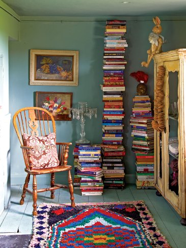 English country house interiors: Soaring towers of books in a cozy turquoise room with framed oil paintings, an antique wooden chair, and a colorful rug on a plank floor painted pale turquoise