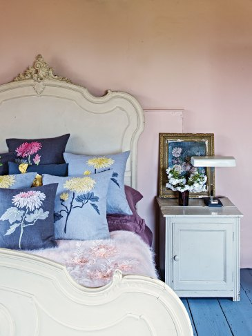 English country house interiors: pale pink bedroom with an ornate bed frame painted soft white, embroidered floral throw pillows, plank floors painted blue, and a bedside cabinet painted white and topped with a vase of flowers, an antique framed botanical oil painting, and a library-style reading lamp