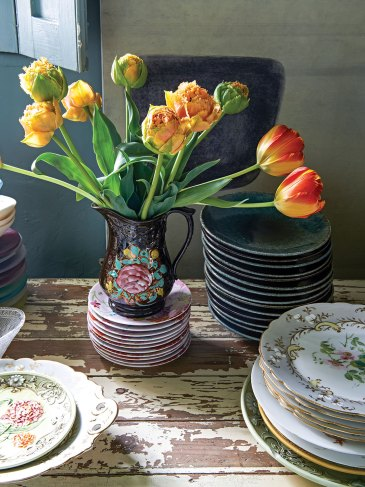 Yellow tulips in a vintage jug bearing a floral motif and stacks of Nikki Tibbles's vintage dinnerware on a rustic wooden tabletop with distressed white paint