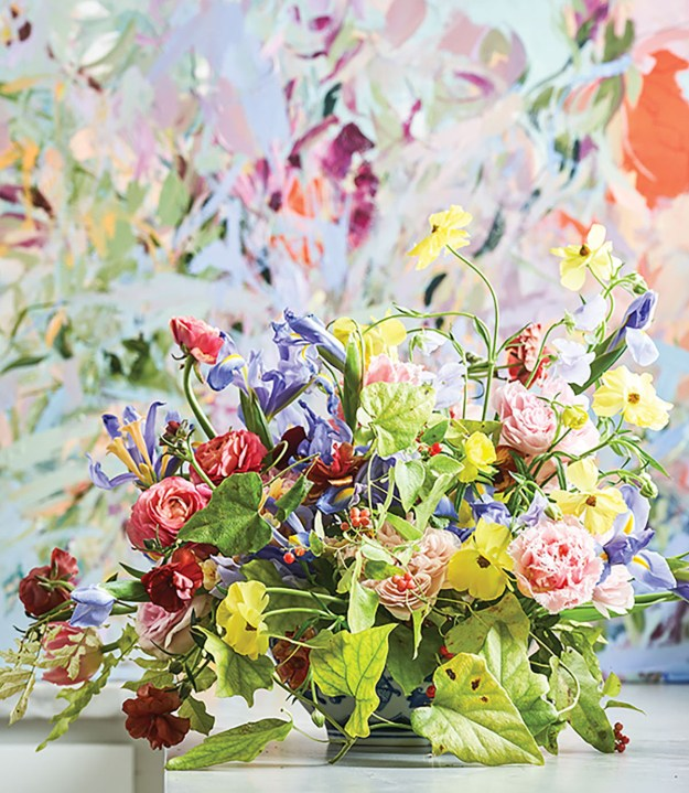 A garden arrangement in a rainbow of colors in front of a Marcy Cook floral painting of the same palette