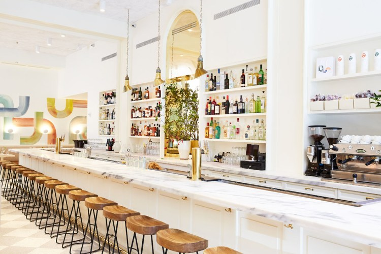 long marble bar inside Il Florista, a restaurant and floral boutique in New York City