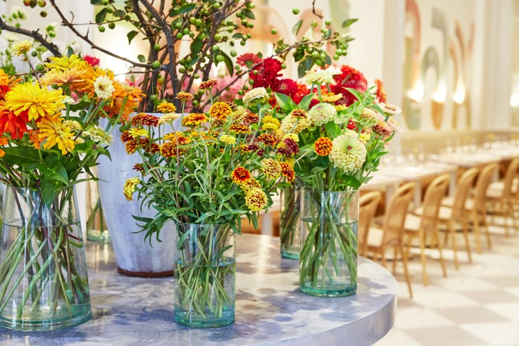 Close up view of vases of colorful zinnias standing on a round table at the entrance of Il Florista in New York City. In the background, you see a long row of tables and chairs on a white-and-pale gray diamond-patterned floor.