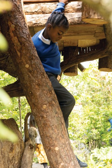 A child descends the treehouse steps of Duchess of Cambridge's Back to Nature Garden