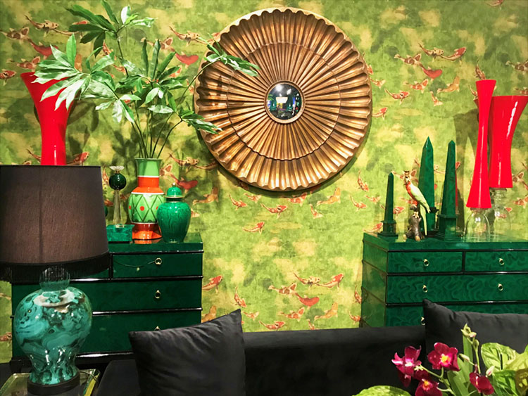 A scene from Maison&Objet features a deep green , lacquered chest of drawers against a tropical-inspired wallpaper