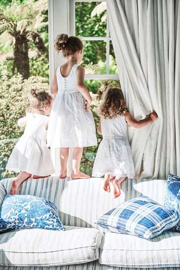3 small children stand and kneel on a sofa back, peering through the window into the gardens