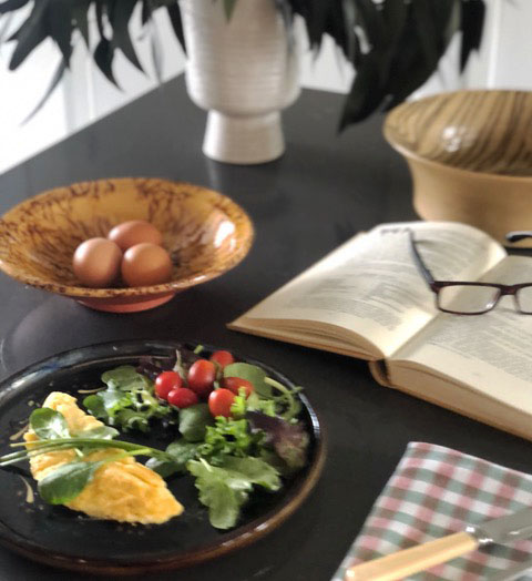 omelet on a table with a book and reading glasses