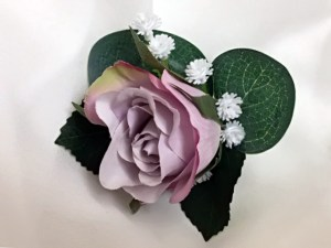Mauve rose bud button hole with rose leaves, gum and baby's breath.