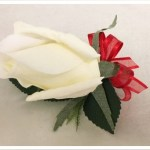 White rose buttonhole with red organza bow.