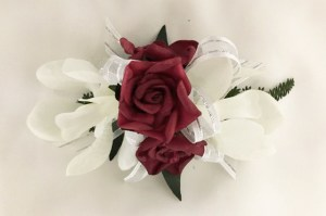 White orchid with deep red rose corsage with white organza ribbon with silver thread.