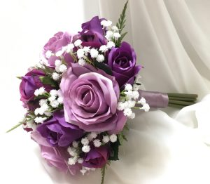 Natural posy style bridesmaids posy in mix of mauve and purple roses, greenery and baby's breath.