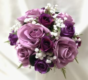 Bridesmaid posy with mix of mauve and purple roses, baby's breath and greenery.