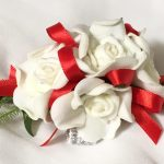 White roses with bright red thin satin ribbon.