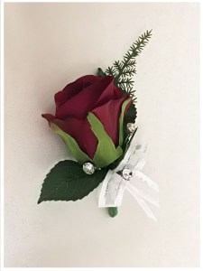 Dark red rose buttonhole with added bow and silver diamantes.