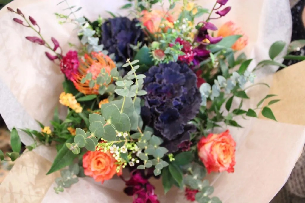 Dark purple, orange, hot pink, splash of yellow with greens floral bouquet in a paper wrap.