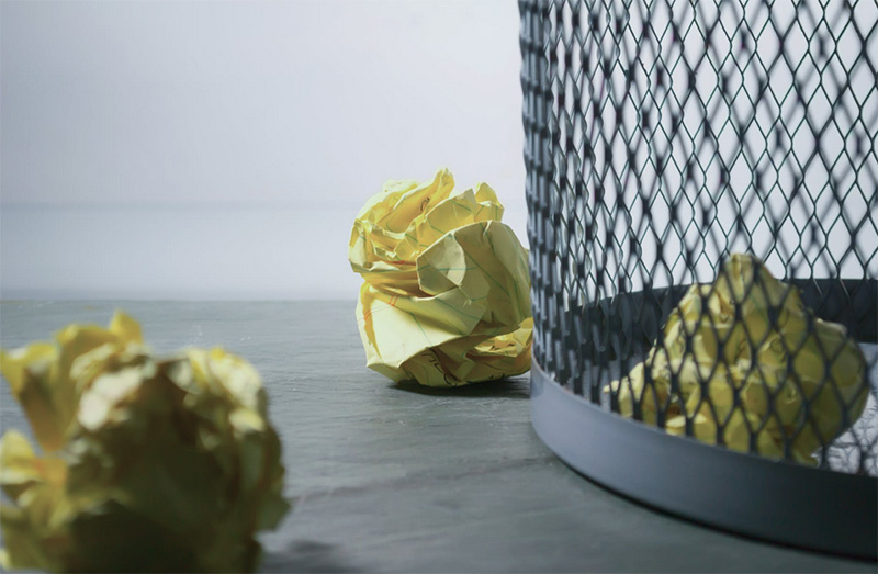 Wastebasket with crumpled pieces of paper beside it