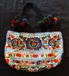 Embroidered purse with pom poms