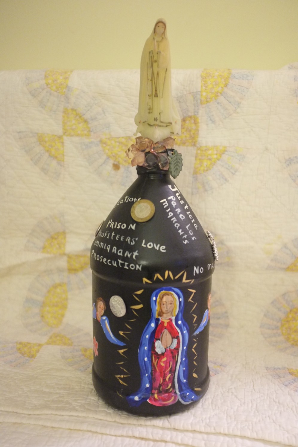 Repurposed water bottle created as memorial tribute to immigrants lost in the desert crossing to the border. From a series produced by the aid group Los Samaritanos. Items attached to the bottle include found objects from the trail and others, including an earring, Mexican currency, a plastic calaveras, milagros, statements of protest, a painted image of OL of Guadalupe. Surmounted by a small glow-in-the-dark plastic figure of the of the Blessed Mother. Gift from artist Juanito Jiménez, New Mexico, 2014.