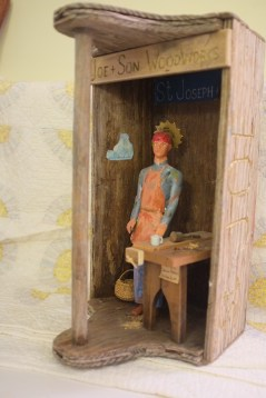 "Assemblage: St. Joseph the Carpenter by Chris Radus, from a series entitled ""Working Class Saints."" Niche is an upended aged wooden tool carrier representing a carpenter's workshop, with worktable, coffee cup, basket for shavings, and sign ""Joe + Son Woodworks . Saint is an embellished GI Joe wearing jeans, leather work-apron and hair-protecting bandanna. Halo is a radial-saw blade. Gift to the collector, 2014."