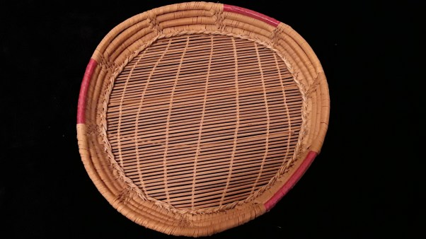 "Kiliru (tool for making pasta). 12"" in diameter; reed and raffia. Castelsardo, Sardinia (Italy), ca. 1986. No Sardinian kitchen was complete without one of these tools, used to shape small bits of dough into a characteristic Sardinian form variously called cicciones, culungiones, malloreddus, and by many other names. They look like tiny ridged dumplings, and are made by curling the dough against the reeds in the bottom of this basket-like object. Cicciones are a key part of festive meals in many parts of the island. The women of Bessude make cicciones for the town's patronal feast of the Assumption of the Virgin (15 August), and today for a new cicciones festival that takes place the weekend before the festival, drawing more tourists into the town. Like many baskets, kiliros are made in Castelsardo, a town on the island's northern coast, where many craftspeople specialize in this art."