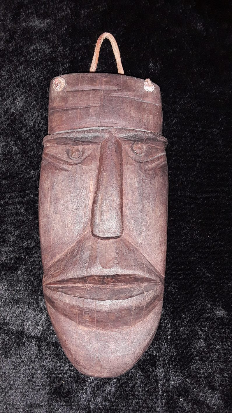 """Mammuttone mask, by Vincenza Carboni. 7.25"""" x 3.5"""" x 1"""". European live oak with dark stain. Bessude, Sardinia (Italy), 1986. Mammuttones are Sardinian Carnival characters who wear heavy wooden masks, sheep skins, and large bells on their backs. They represent untamed animal nature and the wilderness. They dance and parade in many towns during Carnival. This small representation of a Carnival mask was carved for me by a key interlocutor in my study of Sardinian festivals and globalization. Wood carving is usually a man's hobby in Sardinia; Vincenza Carboni (1947 - ) or """"E.T.,"""" as she is known in my work, is an exception. She began playing around with carving knives as a small child after watching her brothers and uncles at the craft. A retired math and science teacher who served on the city council and as vice-mayor for many years, she became a skilled carver who has also made furniture and the characteristic carved wooden dowry chests typical of Sardinia. She gave me this mask as a gift before I left the field after a period of nearly a year, saying that by giving it to me, she was also unmasking herself."""
