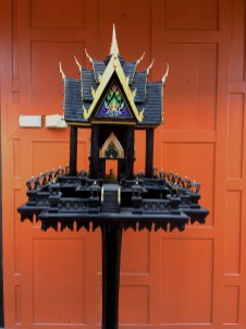 """26"""" x 65"""" x 26"""" Made from Poplar, Pine, and Basswoods. Black enamel with 24K gold accents. The curved points on the ends of the roofs are called Chofa which means """"Sky hooks or Sky Tassels"""" They were believed to anchor the temple to the sky and also prevent demons from landing on the temple. The small tablet shaped decorations on the upper railing are called Bai Sema, and are used to delineate the area within them as holy ground. This took roughly 9 months off and on to complete, and is usually keep inside."""