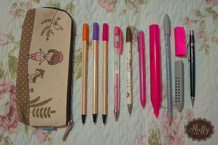 Estojo com: canetas coloridas + caneta gel na cor rosa + caneta preta + caneta simples na cor rosa + marcador de texto + lápis + post-its + borracha + lapiseira.