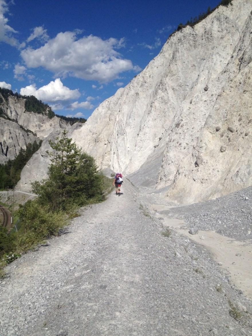 Wanderweg über einen grauen Damm aus Bergschutt. Daneben steile Felsen und ein Stück Himmel. Winzig eine Wanderin.