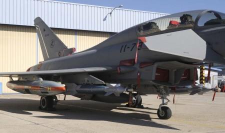 Detalle de la GBU-48 bajo el ala izquierda. El pod con la banda naranja y las marcas de calibración contiene cámaras para filmar la bomba en vuelo.