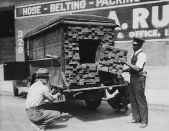 Alertados por el olor de una botella rota de licor, los agentes inspeccionan un 'camión de maderos', Los Ángeles, 1926.