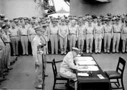 El General Douglas MacArthur firma la rendición oficial de Japón, 1945.
