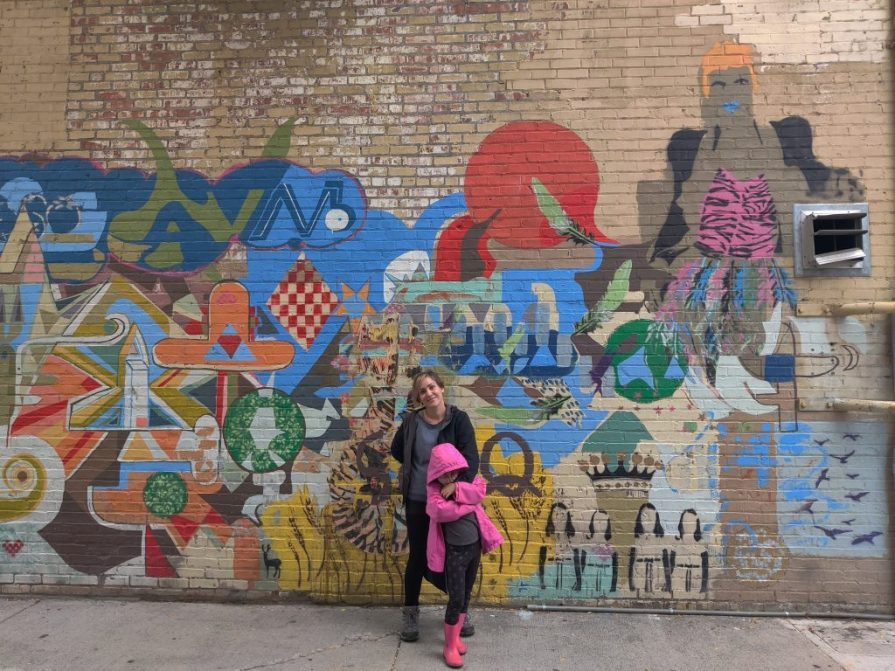 Woman and daughter in front of a colorful mural