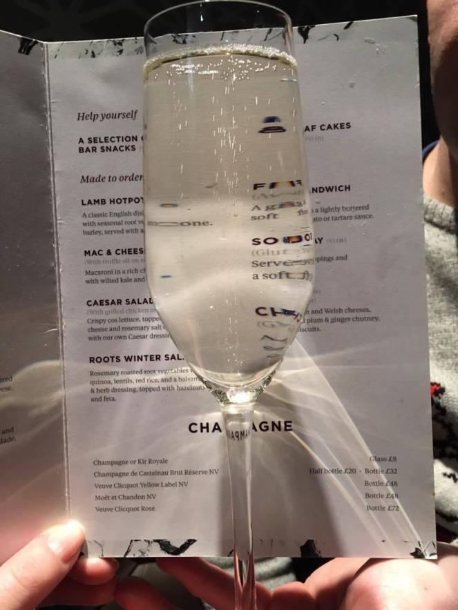 A glass of prosecco against a menu