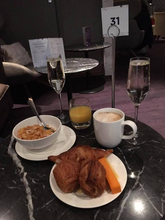 2 glasses of prosecco, a glass of orange juice, a cup of coffee, a bowl of corn flakes and a plate of pastries and a block of red Leicester cheese on a round black marble table