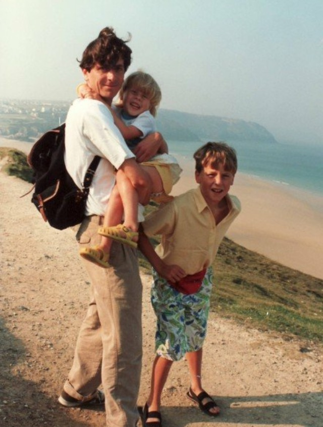 Rosie as a girl held by her step dad, next to her brother at the coast