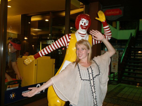 Rosie stands in front of Ronald McDonald's statue, copying it's pose, outside McDonald's in Thailand