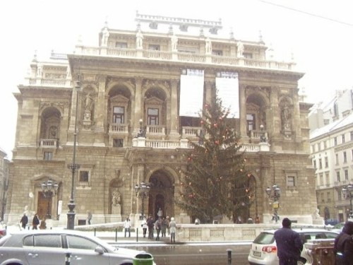 Photo of the front of the Magyar Allami Operahaz, Hungarian State Opera House with a large Christmas outside and snow on the rooftops