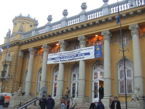 A photo of the entrance to Széchenyi Baths with tall concrete columns fronted by stairs, set against a yellow plaster facade