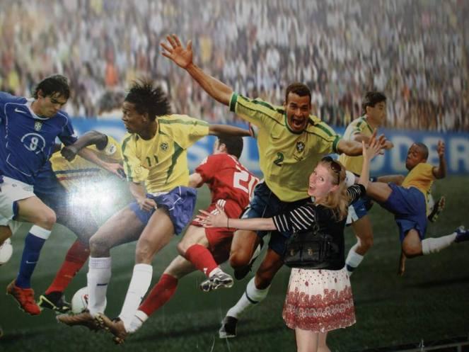 Rosie pretends to hug a footballers photo at the Maracana Stadium, Rio de Janeiro