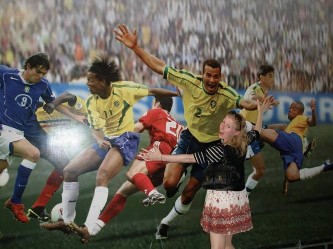 Rosie pretends to hug a footballers photo at the Maracana Stadium, Rio de Janeiro