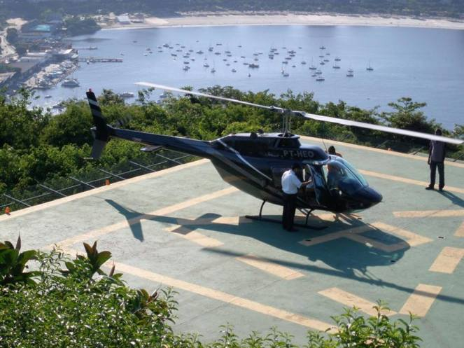 A black tourist helicopter on the pad at Christ the Redeemer, Rio de Janeiro