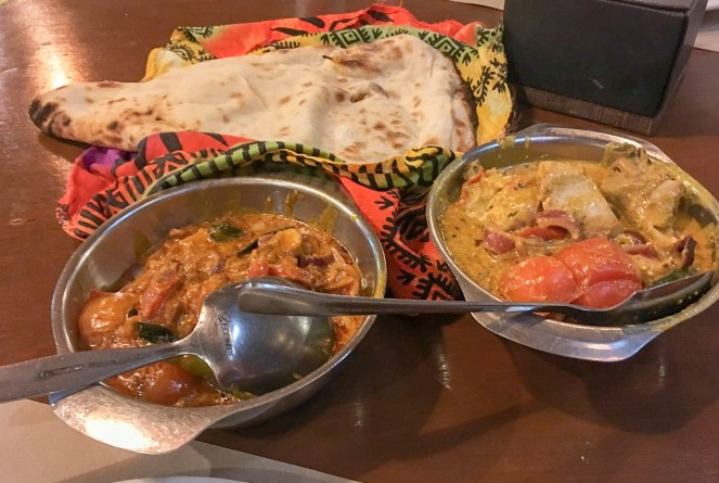 a naan bread in a cloth, a bowl of tomato curry and a bowl of chicken curry