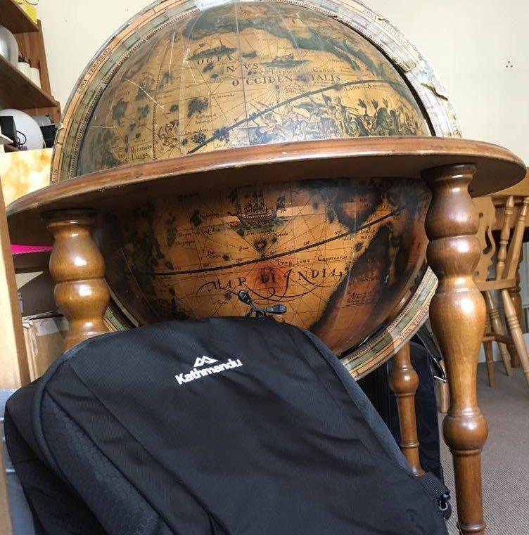 a black Kathmandu Litehaul 38 V3 backpack leans against a wooden globe bar