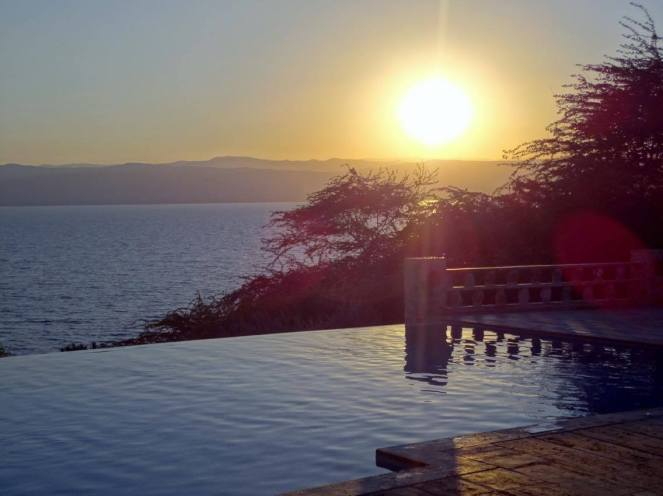 A photo of an infinity swimming pool with the sun setting over the mountains in the background in Jordan