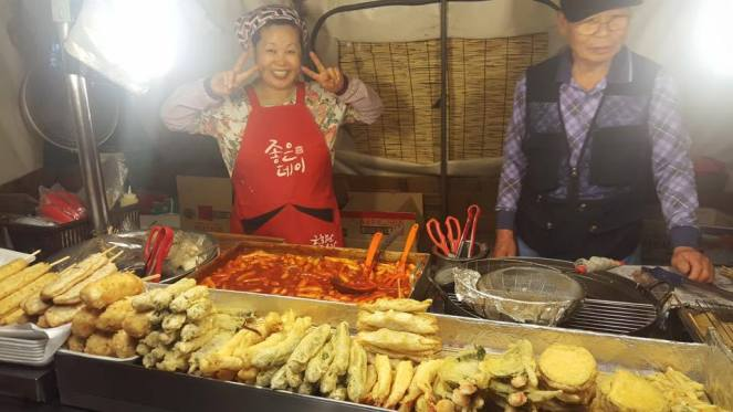 A lady makes a V sign and smiles at a twigim street food stall in Seoul, South Korea