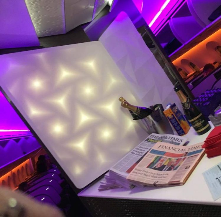 A photo of the Upper Class bar with champagne and newspapers on a Boeing 787