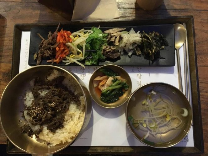 a tray of bibimbap with bronze bowls of bulgogi beef on rice, fermented soy beans and a black rectangular plate of vegetables at Mokmyeoksanbang restaurant, Seoul, South Korea