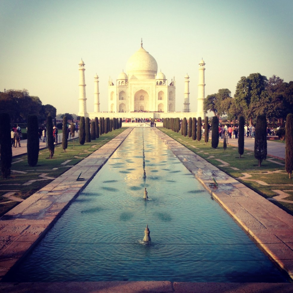 A photo of the Taj Mahal in the background through the gardens with pool leading up to it