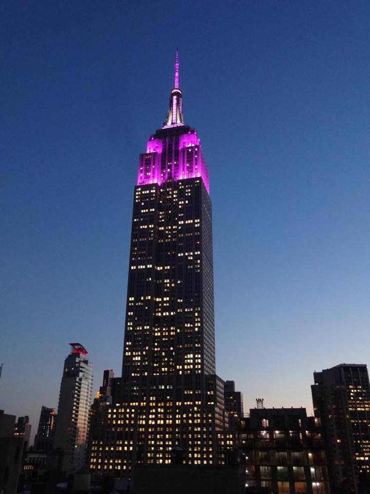 The Empire State Building, lit in purple in New York City at dusk